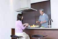 キッチンで料理をしているシニア男性と座っているシニア女性 02336005363| 写真素材・ストックフォト・画像・イラスト素材|アマナイメージズ