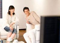 リビングでテレビを観る夫婦