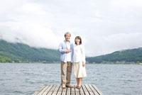 桟橋でカメラを持っているシニア男性とシニア女性 02336005406A| 写真素材・ストックフォト・画像・イラスト素材|アマナイメージズ
