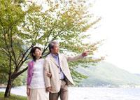湖畔を歩くシニア夫婦 02336005422A| 写真素材・ストックフォト・画像・イラスト素材|アマナイメージズ