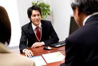 商談をしているシニア夫婦とビジネスマン