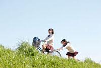 堤防を自転車で走る女子高校生2人