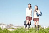 堤防で遠くを眺める女子高校生2人