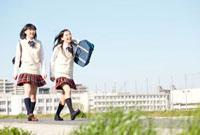 堤防を歩く女子高校生2人