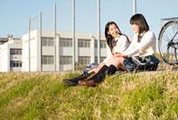 堤防に座って談笑する女子高校生2人