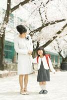 母親と手をつないでいる小学生の女の子