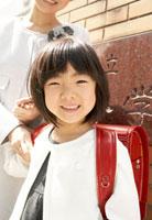 校門の前に立つ母親と小学生の女の子