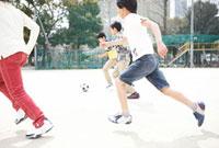 校庭でサッカーをする小学生