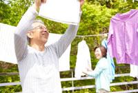 洗濯物を干すシニア夫婦 02336005712| 写真素材・ストックフォト・画像・イラスト素材|アマナイメージズ