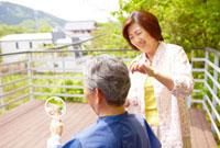 夫の散髪をするシニア女性