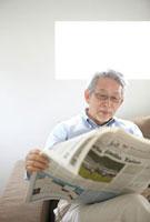 リビングで新聞を読むシニア男性