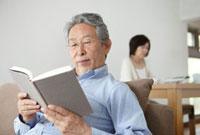 リビングで本を読むシニア男性