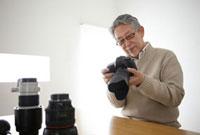 カメラのメンテナンスをするシニア男性