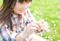シロツメグサの腕輪を作る女の子