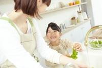 キッチンでグリーンリーフを洗う母親と笑顔の女の子