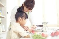 キッチンでトマトを切る母親と女の子