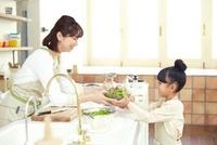 ボールに入ったサラダを母親から受け取っている女の子 02336005997| 写真素材・ストックフォト・画像・イラスト素材|アマナイメージズ