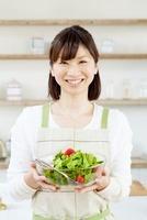 ボールに入ったサラダを手に持っている笑顔の女性