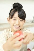 トマトを差し出す笑顔の女の子 02336006000| 写真素材・ストックフォト・画像・イラスト素材|アマナイメージズ