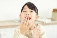 トマトを口いっぱいにほおばっている女の子