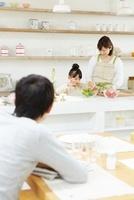 キッチンで料理をしている母と娘を見つめている父親