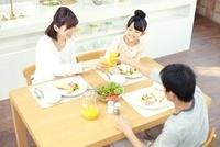 テーブルにのった食事を囲みオレンジジュースで乾杯する家族三人 02336006009| 写真素材・ストックフォト・画像・イラスト素材|アマナイメージズ
