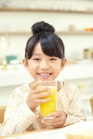 オレンジジュースの入ったコップを手にしている女の子
