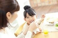 食事中に母親を見ている笑顔の女の子 02336006015| 写真素材・ストックフォト・画像・イラスト素材|アマナイメージズ