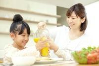 女の子の持つコップにオレンジジュースを注ぐ母親