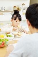 食事をしている娘を見ている父親 02336006019| 写真素材・ストックフォト・画像・イラスト素材|アマナイメージズ