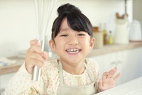 キッチンで泡立て器を手にしている笑顔の女の子