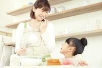 キッチンで泡立て器を持った母親と笑って見合っている女の子