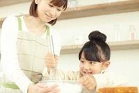 キッチンでボールに入ったクリームを泡立てている女の子と母親