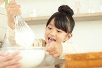 キッチンでボールに入ったクリームを泡立てている女の子 02336006029| 写真素材・ストックフォト・画像・イラスト素材|アマナイメージズ