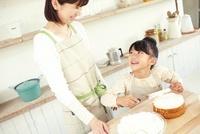 スポンジ生地にクリームを塗る女の子と見ている母親