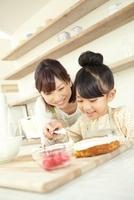 スポンジ生地にクリームを塗る女の子と母親