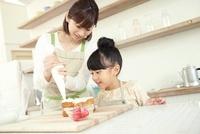 搾り袋でクリームを搾る母親と見つめる寝る女の子