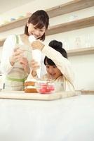 搾り袋でクリームを搾る女の子と母親