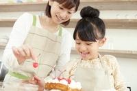 スポンジケーキにチェリーでデコレーションしている女の子と母親