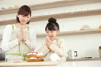 完成したケーキを前に手をたたいて喜ぶ女の子と母親