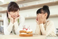 完成したケーキを前に頬杖をついて笑顔の女の子と母親