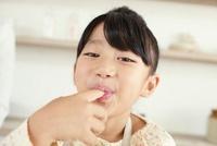 クリームを指に取り舐める女の子