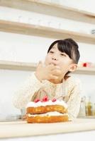 ケーキのクリームを指に取り舐める女の子