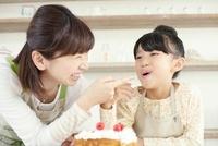 女の子の口に付いたクリームを指差して笑っている母親