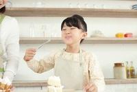 キッチンでケーキをほおばる女の子
