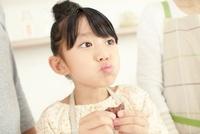 焼き上がったクッキーをほおばる女の子 02336006063| 写真素材・ストックフォト・画像・イラスト素材|アマナイメージズ