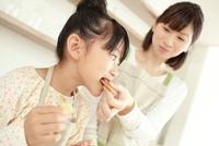 焼き上がったクッキーを母親に食べさせてもらっている女の子 02336006064| 写真素材・ストックフォト・画像・イラスト素材|アマナイメージズ
