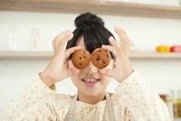 焼き上がったクッキーでおちゃらけている女の子 02336006065| 写真素材・ストックフォト・画像・イラスト素材|アマナイメージズ