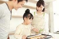 焼き上がったクッキーを見ている父母と女の子