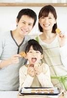 焼き上がったクッキーを手にして笑顔の父母と女の子